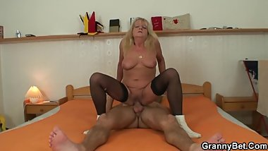 Blonde saggy old granny has sex with a young man on a bed.